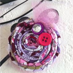 Rolled fabric flower with buttons, jewel, & tulle accents. This is a clip that can be worn by itself, in a group of clips or on a headband. From infants (on a headband) to adults.