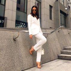 Женский деловой костюм с зауженными брюками белого цвета.
