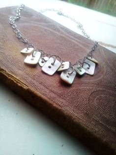 Necklace / white buttons / silver chain necklace via Etsy.