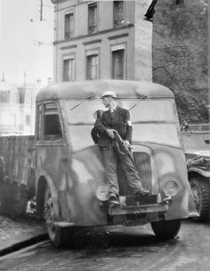 FRENCH RESISTANCE 1944: A member of the French Forces of the Interior (FFI) armed with a Sten gun, uses a truck for cover during gun battles with German snipers in Dreux. During this period several French towns were liberated by the FFI in advance of Allied forces.