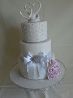 #White #bling #bows #hearts #pearl dots #silver shimmer & broach with pinky/purple roses created by MJ www.mjscakes.co.nz in sunny Hawkes Bay NZ delivered to the elegant  old church Purple Roses, Mj, Wedding Cakes, Hearts, Dots, Bling, Elegant, Silver, Dapper Gentleman