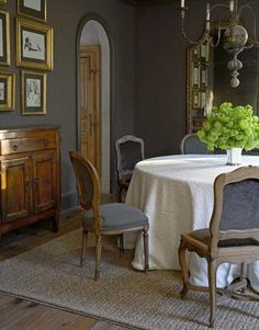 gray dining room. grey dining room.  jute rug, charcoal gray walls paint color, chandelier, french chairs and buffet.