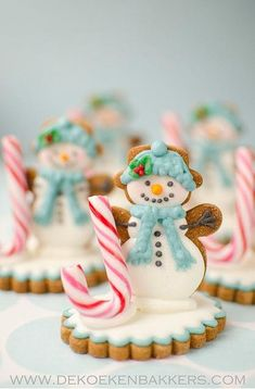 Intricately decorated, this cookie snowman stands upright, holding a candy cane on a cookie base.