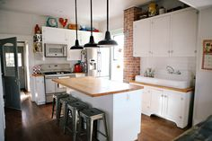 Farmhouse style kitchen renovation - white painted cabinets, butcher block countertops, industrial bar stools
