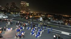 An event at night on the flight deck of floating aircraft carrier museum USS Midway with San Diego skyline in the background - Photo by Patty Mooney of video production company Crystal Pyramid Productions