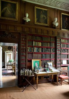 16th century portait paintings hang below an ornate plasterwork cornice in the library  Badminton House