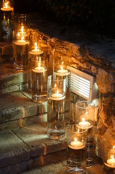 Single floating candles in narrow glass hurricanes illuminate stone steps for guests.