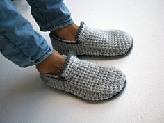 Crochet slippers with thick dark gray felt soles. The slippers are made with a…