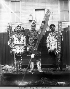 Three men in ceremonial regalia carrying song leaders staffs; 1904 potlatch, Sitka. :: Alaska State Library-Historical Collections