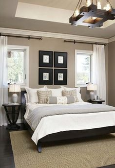 rustic overhead lighting, light grey and white bedding, neutral walls, black headboard framing, wood flooring and tan area rug. same idea as their bedroom.