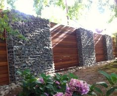 Gabion fence with timber Built using rounded river cobbles 4.5mm welded mesh 75mm x 75mm Pictured 2rows of 1500mm wide by 1050mm tall gabions Gabions supplied in kitsets delivered to your door Easy to assemble and low cost stone fences Check out the retaining wall design guidelines Check out our 100's of prices and sizes