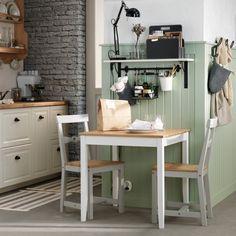 Un coin repas avec une table chaleureuse. Petit espace et petit coin repas ne sont pas synonymes de froideur insipide. Ce lambris vert d'eau, ce mur en briques, accompagnés d'une table carré au bois blond apportent chaleur à cette petite cuisine fonctionnelle.