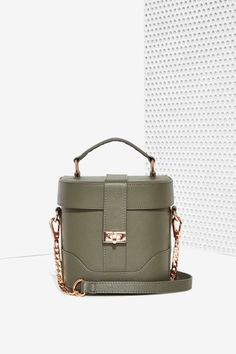 The Awe Structured Bag comes in olive green leather and features a structured bucket design, top flag, rose gold lock closure and chain strap.