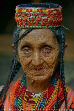 An elderly Kalash woman from Pakistan with an impassive expression, yet intense pale green eyes in her colorful headdress, & bead necklaces Old Faces, Many Faces, Beautiful Eyes, Beautiful People, Amazing Eyes, People Around The World, Around The Worlds, Kalash People, Interesting Faces