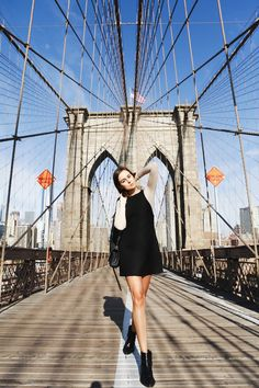 Andy Torres wearing an H&M Studio black dress and Ganni top at the Brooklyn Bridge in New York.