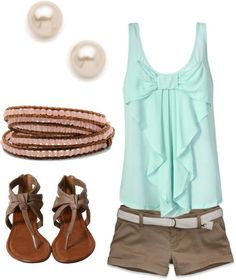 blue top, pearl earrings, and gray shorts