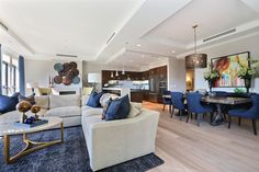 This unit features an open floorplan utilizing deep hues of denim-colored dining chairs and accents throughout. All furniture and decor provided by HW Home, a Colorado company.