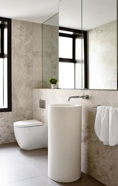 The powder room clad in limestone tiles   Walsh Street project by Neometro together with the Carr Design Group and MA Architects
