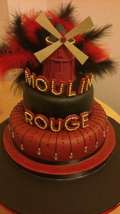 Moulin Rouge Cake by Sharon Bailey Lots of trail and error in this cake and the sails would stick on when made of flowerpaste, and when they finally did one snapped off :( ended up with gold card sails but still looks good.