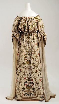 """Embroidered """"medieval"""" fancy dress costume by House of Worth, French, 1900-05. Made of silk, metal, imitation pearls, rhinestones, and wood (for the sticks of small green flags carried as part of the costume)."""