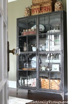Love this metal glass front industrial cabinet - perfect for storage and display in the dining room including a fun collection of corks in huge glass jars from HomeGoods. sponsored pin eclecticallyvintage.com