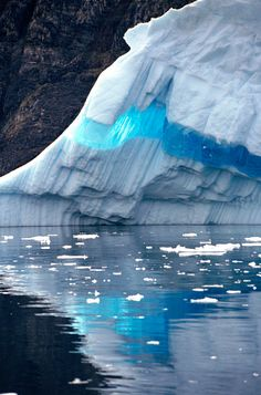 A ribbon of clear blue ice runs through an iceberg and is reflected in the sea. West Greenland