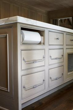 Topped with a marble countertop, this gorgeous rift saw oak kitchen island is completed with flat face drawers adorning satin nickel hardware and fitted with a paper towel dispenser.