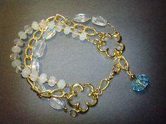 Bracciale con acquamarina e cristallo, montato con catena, inserti e componenti in metallo color oro. Realizzazione artigianale.