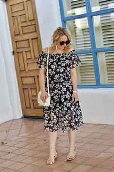 Off the Shoulder Navy Floral Dress: A cool, flowy dress for summer styled with beige studded sandals, white tassel earrings and a white crossbody bag.