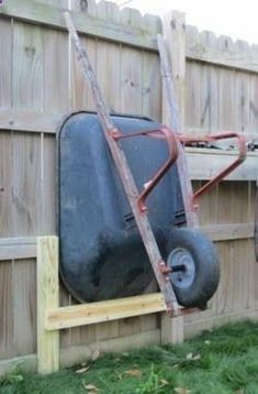Shed Plans - I wanted to raise my wheelbarrow up to make it easier to mow around. Here is a quick way to store a wheelbarrow next to a fence. - Now You Can Build ANY Shed In A Weekend Even If You've Zero Woodworking Experience! Backyard Projects, Garden Projects, Wood Projects, Outdoor Projects, Outdoor Ideas, Backyard Ideas, Wheelbarrow Storage, Garage Tools, Garage Shop