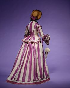 "Day Dress: early 1860's, Italian, striped silk taffeta bodice and skirt, frills on bodice and skirt hem. ""A dress featuring bold stripes in purple, the fashionable color during that era. In 1856, the chemist William Perkin (1838-1907) discovered the world's first synthetic dye, mauveine. This was soon adapted into textile dyeing and the color which resulted, termed ""mauve"", before long attracted a great deal of attention..."""