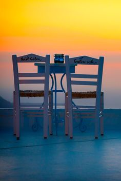 Two chairs facing the sunset in Santorini Island