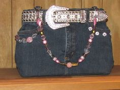 Blue jean purse is 12 inches wide x 9 inches long.  With flexible sides and a supportive bottom.  The inside material colors are of pink, blue, green and white with a flower print.  There is 1 inside pocket and 4 outside pockets.  A magnetic snap is on the inside of purse for closure.  Handle is made with an assortment of glass, metal and plastic beads.  The outside of purse is decorated with a white blingy belt and decorations are on front and back of purse.  $197.00 + tax, shipping…