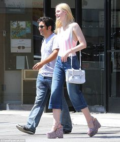 Keeping it casual: Elle Fanning was casual yet chic in a pink and white vest top and denim...