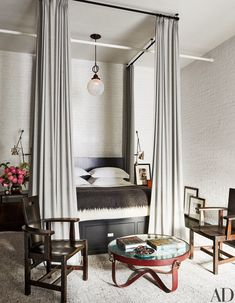 Bed curtains of a Holland & Sherry wool and a pendant light from Olde Good Things hang in the master bedroom. Arts and Crafts chairs by George Henry Walton, cocktail table by Jacques Adnet, rug by RH.