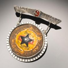"""Robert Dancik: """"They knew he was serious when Sheriff Jim wore his black star"""" Pin in sterling silver, bottle cap, aquamarine, carnelian, polymer clay and 14k gold."""