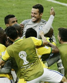 Brazil's goalkeeper Julio Cesar, top, is congratulated by his teammates after the World Cup round of 16 soccer match between Brazil and Chile at the Mineirao Stadium in Belo Horizonte, Brazil, Saturday, June 28, 2014. Brazil won 3-2 on penalties after the match ended 1-1 draw after extra-time.