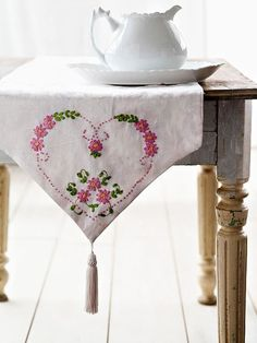 Embroidered table runner and white pitcher.