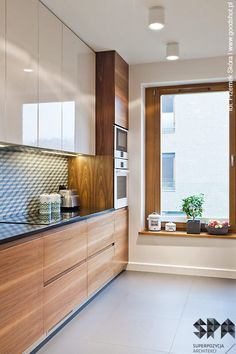 modern gray kitchen features dark gray flat front cabinets paired with white quartz countertops and a gray mosaic tiled backsplash - Modern Kitchen Cabinets Images