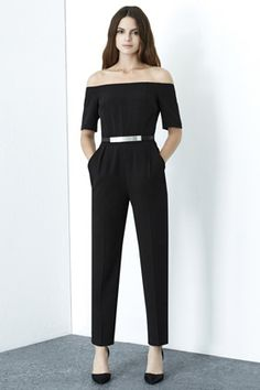 This sleeveless jumpsuit features a high neck, nipped-in ...