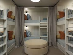 U shaped boys' bedroom with tongue and groove walls, white built-in bunk beds, gray linen curtains, blue bedding, yellow & orange pillows, white ladders and cream round storage ottoman.