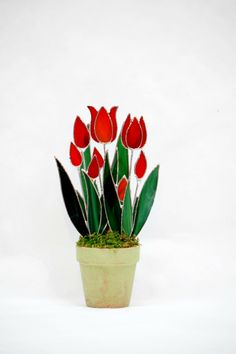 This 3d in full bloom potted handcrafted tulip suncatcher is sure to be the center of attention in any decor. Modeled after a wild species of tulips this selection is a intense red whispy glass that glows in direct sun, highlighted by the deep green glass leaves. Perfectly suitable for desk, work station, window etc. it is attractive in both normal lighting as well as direct sun. Set in stone with moss accents it is sturdy and will last for years. Overall height is 11 tall by 6 wide. Give…