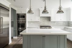 White and grey kitchen features white perimeter cabinets paired with white quartz countertop and a ...