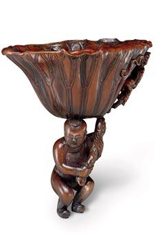 A VERY RARE RHINOCEROS HORN LOTUS LEAF CUP  17TH/18TH CENTURY  The large lotus leaf carved and undercut at one end with water weeds and raised on a curved stem held by a crouching boy  5 1/8 in. (13 cm.) high, box