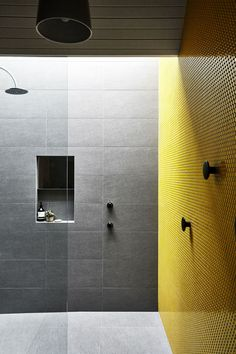 Yellow is the owners' favourite colour and is used in the bathroom tiles, and in a ceramic pendant light, 'Popper' by Lab de Stu, as well as in other elements throughout the house.