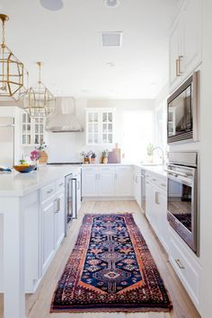 New traditional kitchen, with bright gold and brass lanterns, circa lighting in the ceilings, vintage navy blue and pink Persian runner, bikini stools, brushed brass hardware and white glass front cabinets.