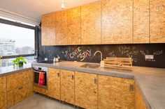 Kitchen cabinet doors made from oiled chipboard and a concrete worktop.