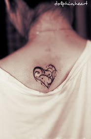 A dolphin tattoo design in the shape of a heart while combining with the waves.