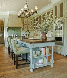 A wonderful kitchen for entertaining family and friends. Antiqued strié painted cabinets with stained cane inserts give a rustic feel to the area as does the v-grooved plank wood ceiling with its light paint wash.