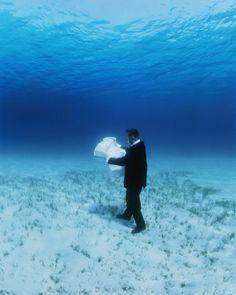 artiste contemporain Philippe Ramette, photographie, un homme qui marche, carte à la main, sur la profondeur de la mer en cherchant à l'explorer